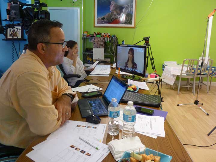 Two people on the production team sitting at a table in the brightly colored video production studio. There is a monitor on the table with the face of an actor. The table is covered with equipment and casting notes.