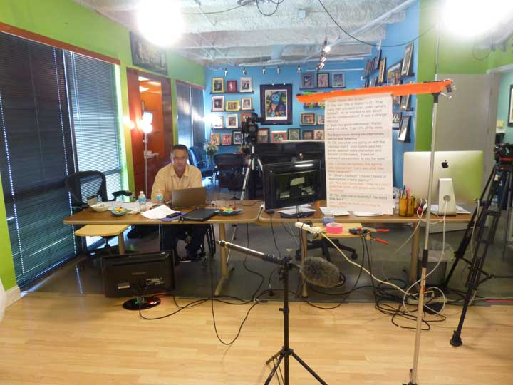 A wide-shot of a brightly colored and well eqiupped video production studio.