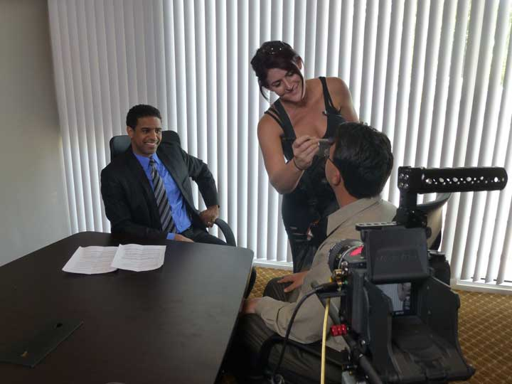 Three people in a conference room that is being used as a video set. A make-up artists is touching up the make-up of an actor while another actor watches them.